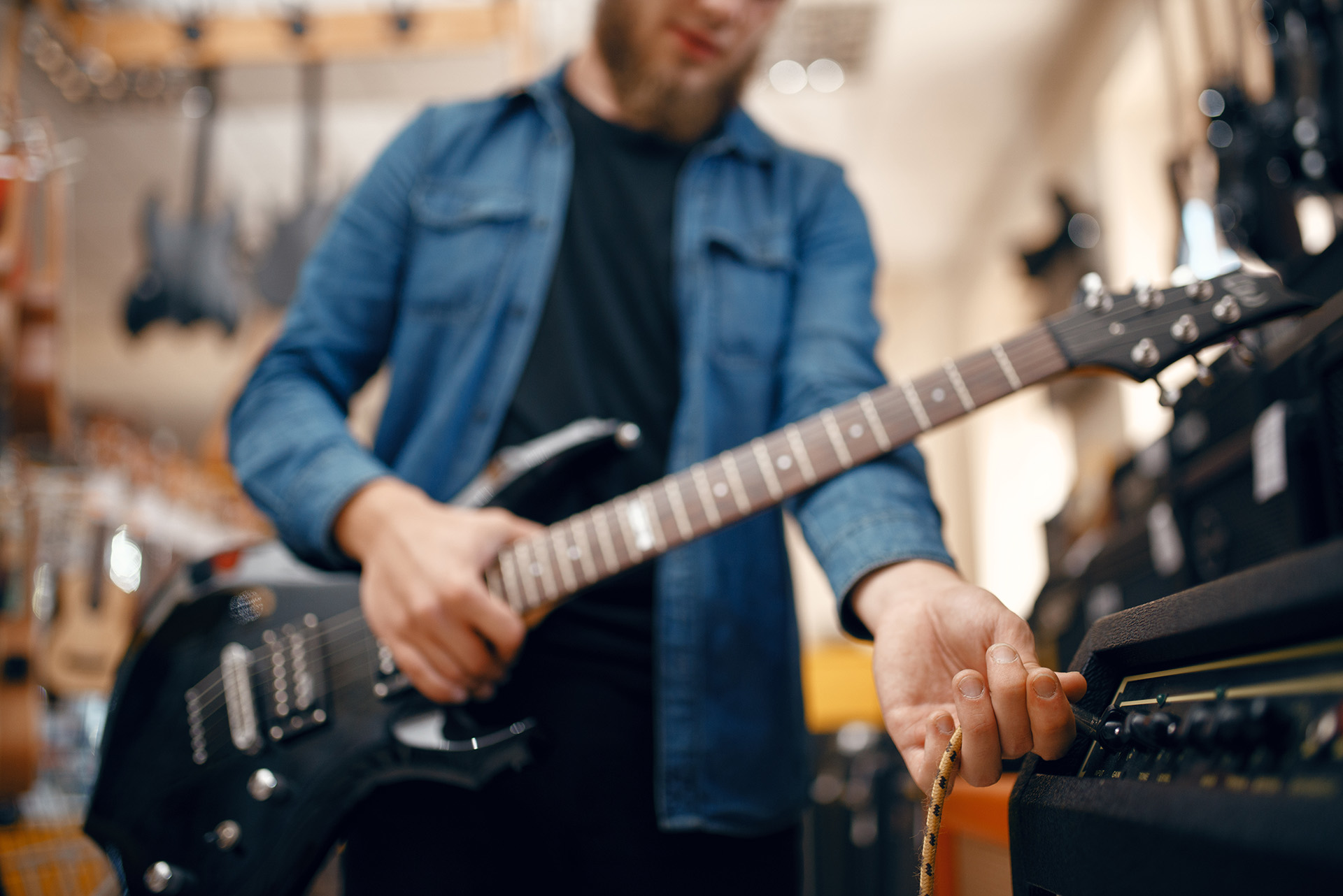 Male guitarist plays on electric guitar in music store. Assortment in musical instruments shop, musician buying equipment