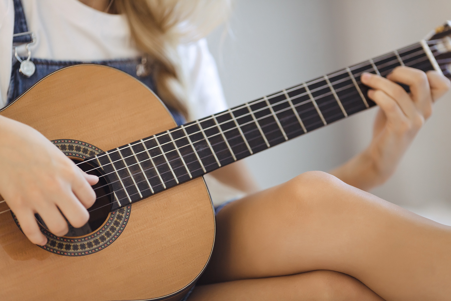Close up of a woman playing guitar at home. Girls's hands playing acoustic guitar indoors.